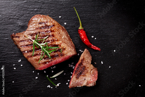 Foto  Grilled beef steak with rosemary, salt and pepper