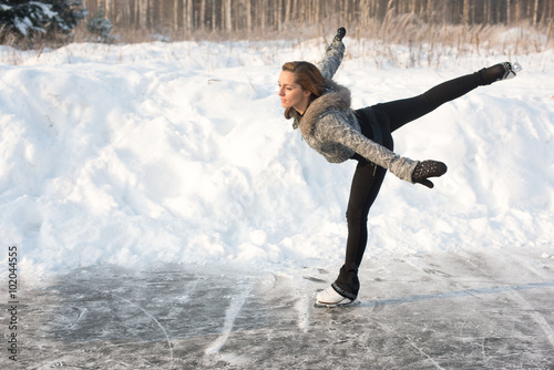 Tuinposter Wintersporten young Figure skating woman at the frozen lake in the winter