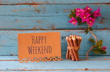 Vintage Card With Phrase: Happy Weekend And Stack Of Wooden Colorful Pencils On Wooden Texture Table Next To Purple Bougainvillea Flower.