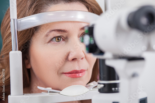 Cheerful lady having eye examination in oculist office