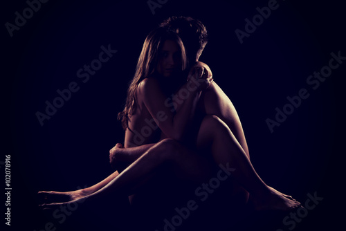 Beautiful nude couple sitting on the floor.