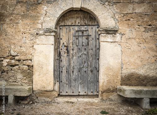 Fotografie, Obraz  Starobylé dřevěné dveře na kameni vyrobený stěn a cementových lavice