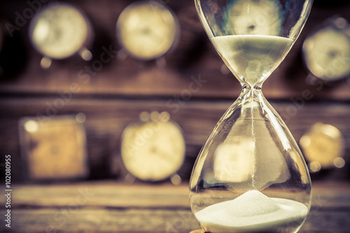 Aged hourglass with flowing sand