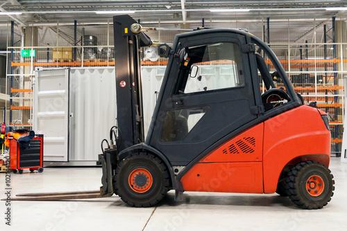 Zdjęcie XXL Pomarańczowy wózek widłowy ładowarka w nowoczesnym magazynie.