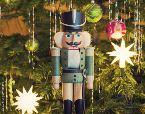 Fotografía  Toy soldier wooden nutcracker statue standing in front of decorated Christmas tr