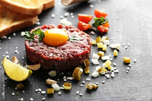 Beef tartare with egg yolk on a black wooden table Wallpaper Mural