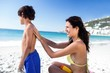 Cute mother applying sunscreen to her son