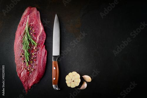 Staande foto Vlees Slice of raw beef steak on dark background. Organic food.