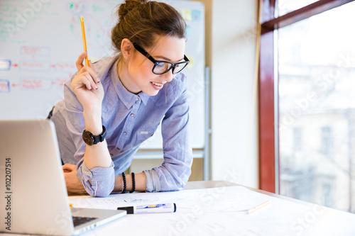 Obraz Happy woman working with blueprint near the window in office - fototapety do salonu