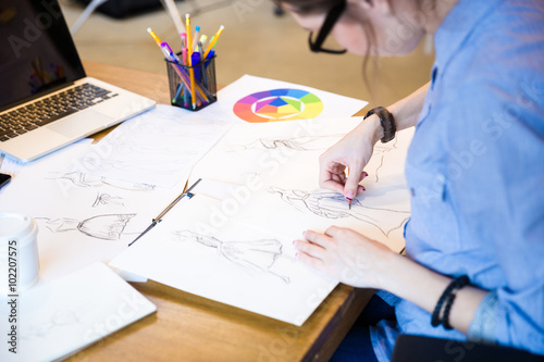 Valokuva  Creative woman fashion designer in glasses sitting and drawing sketches