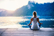 canvas print picture - Yoga lotus. Young woman doing yoga by the lake, sitting in lotus.