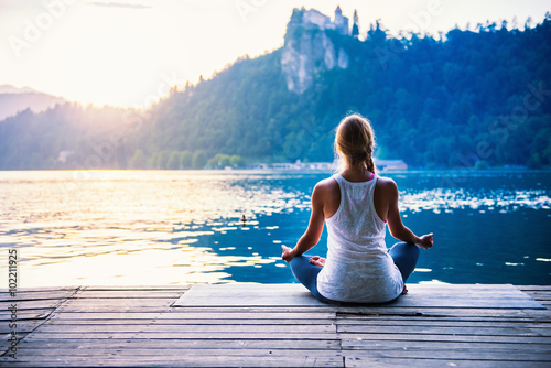 Poster School de yoga Yoga lotus. Young woman doing yoga by the lake, sitting in lotus.