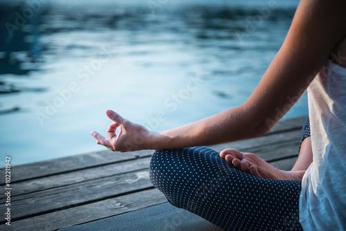 Fotografia  Meditation detail. Woman meditating by the lake