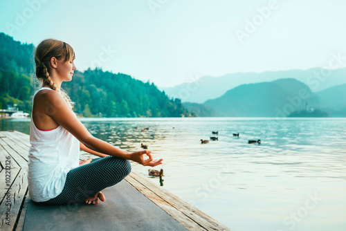 Meditation. Young woman meditating by the lake.