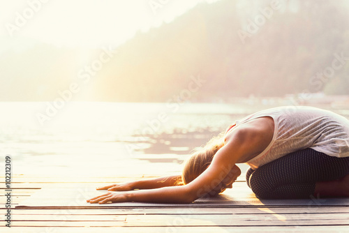 Poster School de yoga Sun salutation yoga. Young woman doing yoga by the lake, bathing in sunlight.