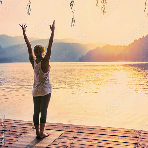 Fototapeta Yoga Sun Salutation. Young woman doing yoga by the lake. Toned image obraz