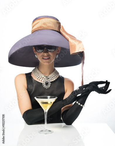 Fotografie, Tablou  A woman in a big hat and sunglasses, like a movie star, drinking martinis