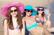 Four beautiful girls in hats sunbathe on the sea beach