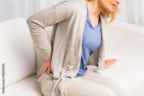 close up of woman suffering from backache at home Canvas Print