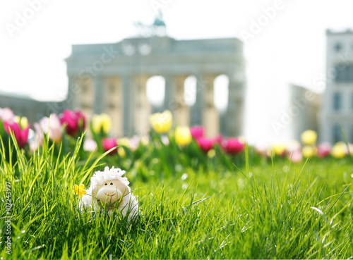 easter in Berlin, toy sheep hiding in green grass with Brandenburger Tor and a fountain