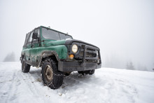 Green Old Off-road Vehicle On The Snow-covered Mountain