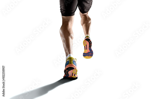 Fotografía  strong athletic legs with ripped calf muscle of young sport man running isolated