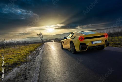 plakat gelber Supersportwagen auf Pfälzer Landstraße vor Sonnenuntergang