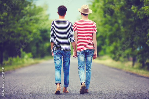gay couple walking away together on spring road Canvas Print