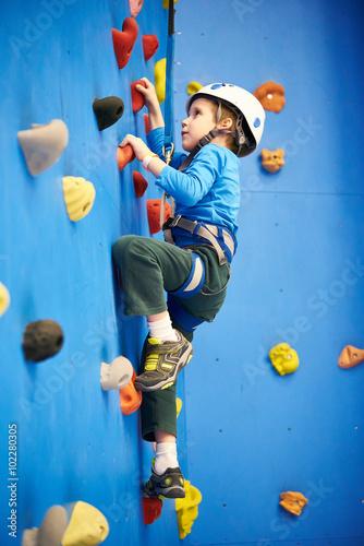 Fotografie, Obraz  Little boy is climbing on blue wall