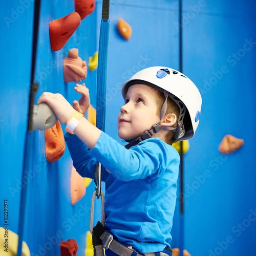 Fototapeta Little boy is climbing in sport park on blue wall obraz