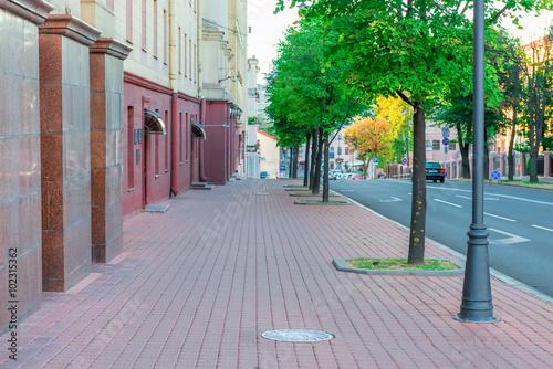 Fotografiet Cityscape - the sidewalk along the road