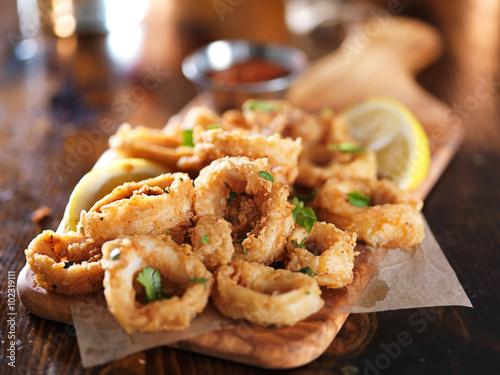 Fototapeta crispy calamari rings on woodne tray with lemon wedge obraz