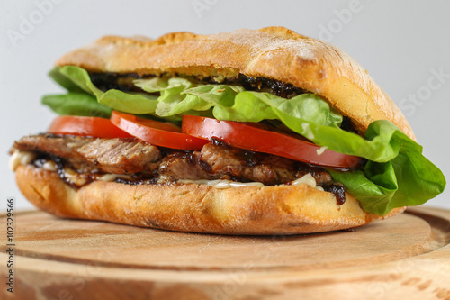 Tasty pork steak sandwich in a ciabatta with tomatos, lettuce, mayonnaise and barbecue sauce