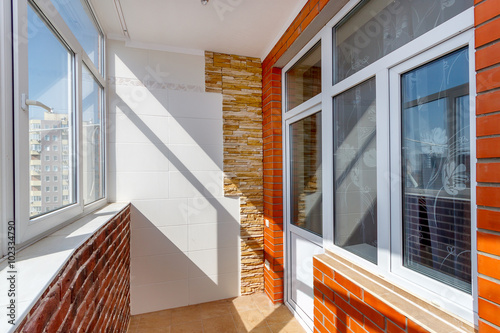 Sunny balcony with plastic windows and door