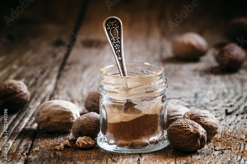Fototapeta Ground nutmeg in a jar and whole nuts on an old wooden backgroun obraz