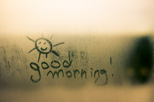 Happy Sunny Face Sign With Good Morning Written On Foggy Window Background.