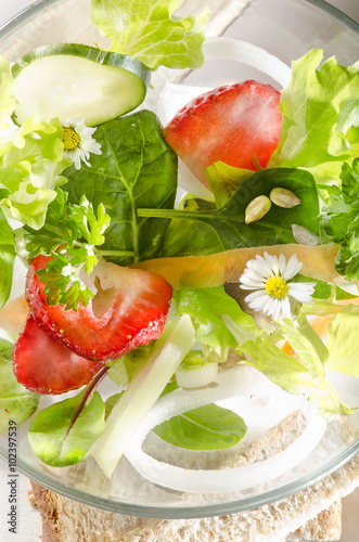 Photo  Frühlingssalat mit frischen Erdbeeren und Gänseblümchen