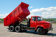 Red Dump Truck With The Body Lifted For Unloading.