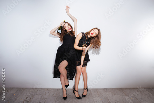Fotografering  Two beautiful drunk women drinking champagne over white background