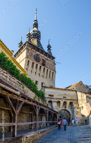 Fotografie, Obraz  Clock tower sided by old building inside medieval town of Sighisoara, Transylvan