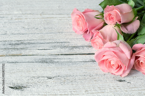Vintage background / postcard / greeting card. Pink roses on white textured wooden background. Copy space, top view