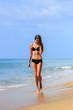 Slim happy girl walking in the beach shore