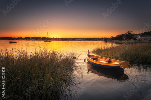 Fotografia  Small Boat in Harbor at Sunset