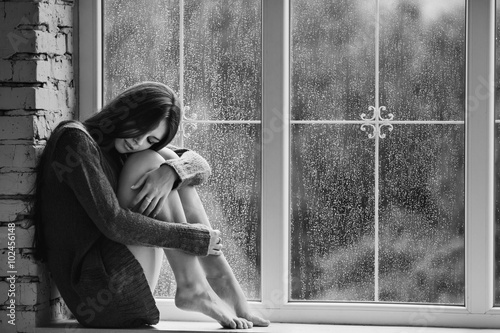 Fotografia  Beautiful young woman sitting alone close to window with rain drops