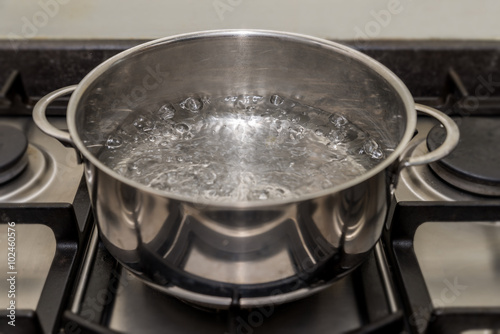 Fotografering  Metal cooking pan with boiling water on a stove