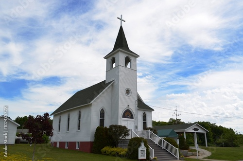 Traditional style architecture Christian church and steeple against a summer sky