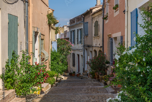 Bended street with coloured houses and flowers in Arles, France on a sunny day i Canvas Print