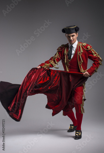 Deurstickers Stierenvechten Studio shot of man dressed as Spanish torero, matador, bullfighter. Performing a traditional classic bullfight, standing and holding the capote.