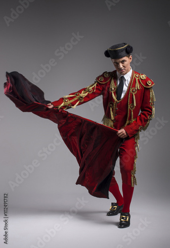 Foto op Plexiglas Stierenvechten Studio shot of man dressed as Spanish torero, matador, bullfighter. Performing a traditional classic bullfight, standing and holding the capote.