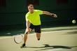 Man plays tennis in bright cloth